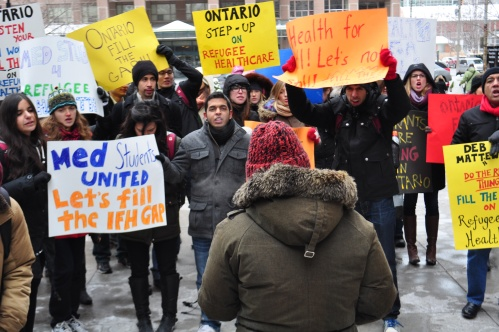 Protesters demand Deb Matthews fills the gap in health care coverage created by Federal cuts to refugees.