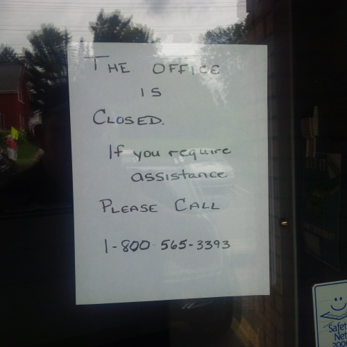 Picture of a hand-written sign saying the ParaMed Office is closed. Thos who need assistance should call 1-800-565-3393.