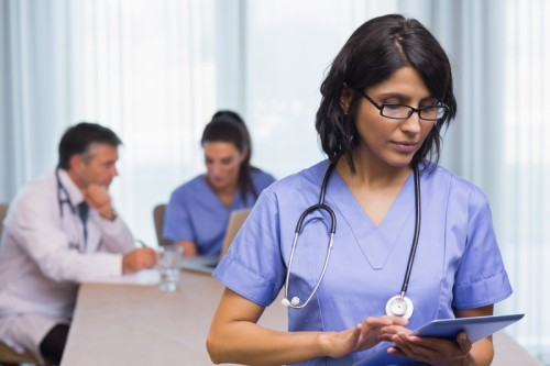 Stock photo of a nurse with a tablet used to illustrate a shortage of nurse practitioners and other professionals in the pimary care sector.