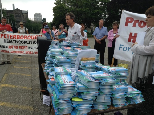 Photograph of table with thousands of cards on it while an unidentified person speaks at a nearby podium. July 8 the Ontario Health Coalition brought more than 80,000 signed cards to the Ontario legislature opposing the transfer of clinical services from hospitals to private clinics.