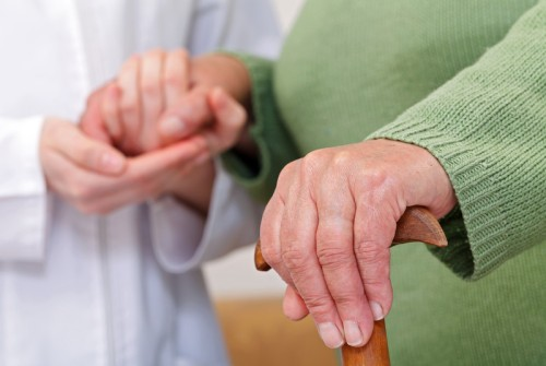 Photo of hands of health professional assisting an elderly female patient.