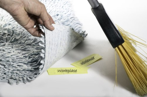 Photograph of person sweeping two post-it notes under a rug. One says Workplace, the other violence.